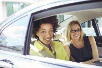 Mujeres empresarias sonriendo en la parte trasera de automóvil - foto de stock