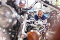 Старший механик мотоцикла работает в мастерской — стоковое фото