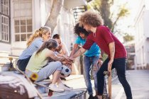 Friends with soccer ball and skateboards touching hands in huddle on urban steps — Stock Photo