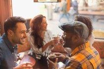 Друзья, говорить и пить кофе в кафе — стоковое фото