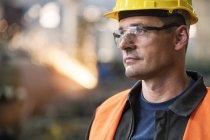 Close up pensive steel worker looking away — Stock Photo