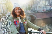 Portrait smiling young woman along urban canal, Amsterdam — Stock Photo
