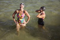 Laughing female open water swimmers wading in sunny ocean — Stock Photo