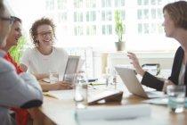 Люди говорять і посміхаючись під час ділової зустрічі в офісі — стокове фото