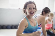 Portrait smiling, laughing woman drinking water and resting post workout at gym — Stock Photo