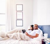 Smiling couple relaxing, reading book in bed — Stock Photo