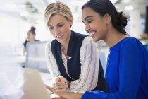Mulheres de negócios usando laptop juntos a sorrir — Fotografia de Stock