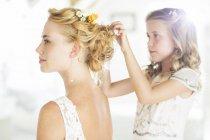 Dama de honor ayudando a la novia con peinado en ambiente doméstico - foto de stock
