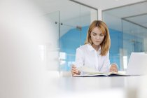 Акцентированная деловая женщина рассматривает документы на ноутбуке в конференц-зале — стоковое фото
