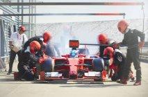 Ravitaillement en travaillant sur la voiture d'une course formule dans la voie des stands — Photo de stock