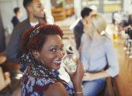 Porträt einer lächelnden Frau, die Wasser trinkt und mit Freunden an der Bar spricht — Stockfoto