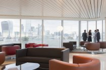 Business people talking at window in urban highrise office lounge with city view — Stock Photo