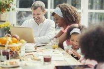 Улыбающийся молодой многоэтнического семьи с помощью ноутбука и едят завтрак за столом — стоковое фото