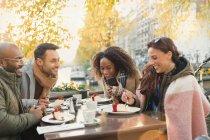 Freunde essen Käsekuchen-Dessert im Herbst-Bürgersteig-Café — Stockfoto