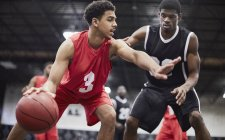 Молодой баскетболист капает мяч, защищая от защитника в баскетбольной игре — стоковое фото