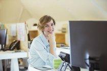Porträt einer lächelnden Frau im Büro, die am Schreibtisch mit Computer sitzt — Stockfoto