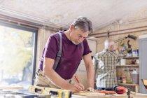 Menuisier mâle mesurant et marquant la planche de bois sur établi en atelier — Photo de stock