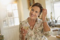 Portrait smiling mature woman drinking white wine in kitchen — Stock Photo