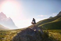 Jeune homme accroupi sur le rocher, regardant ensoleillé, r emote vue sur la montagne — Photo de stock