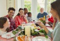 Familia de múltiples generaciones multiétnica disfrutando de una cena de Navidad en la mesa - foto de stock