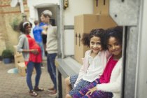 Portrait smiling sisters sitting in moving van outside new house — Stock Photo