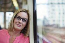 Mujer sonriente mirando a la ventana del tren - foto de stock