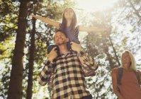 Батько, несучи дочка на плечі, походи в Сонячний ліс — стокове фото