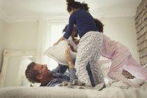 Игривый мультиэтичный отец и дочери подушки борются на кровати — стоковое фото