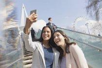 Enthousiaste, souriant amis femmes prenant selfie avec téléphone appareil photo sur les marches ensoleillées, urbains, Londres — Photo de stock