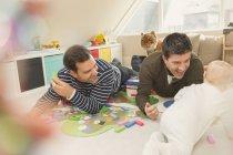Männlich gay eltern spielend mit baby sohn im spielzimmer — Stockfoto