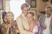 Junges Paar und Gäste bei Hochzeitsempfang im häuslichen Raum — Stockfoto
