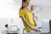 Mother holding baby daughter at laptop — Stock Photo