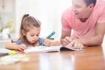 Father watching daughter coloring with crayon and coloring book at table — Stock Photo