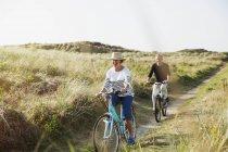 Couple senior bicyclettes à cheval sur le chemin ensoleillé ammophiles — Photo de stock