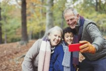 Grandparents and grandson taking selfie in autumn woods — Stock Photo
