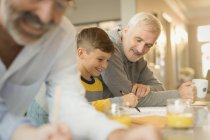 Father helping son with homework at counter — Stock Photo