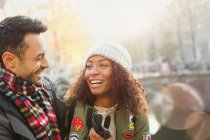 Laughing young couple along autumn canal — Stock Photo