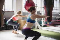 Young women doing squats next to boxing ring in gym — Stockfoto