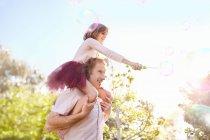 Pai levando a filha com a varinha de bolhas nos ombros, no parque de verão ensolarado — Fotografia de Stock