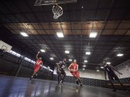 Молодые баскетболисты играют в баскетбол на площадке в тренажерном зале — стоковое фото