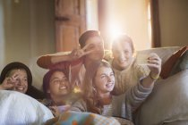 Group of smiling teenagers taking selfie on sofa in living room — Stock Photo