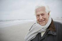 Уверенный в себе пожилой человек в шарфе на зимнем пляже — стоковое фото