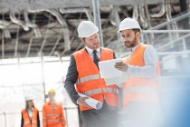 Male engineers with blueprints and clipboard discussing paperwork at construction site — Stock Photo