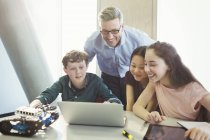 Smiling male teacher and students programming robotics at laptop in classroom — Stock Photo