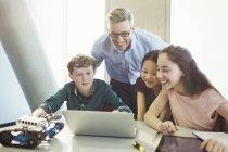 Souriant, enseignant de sexe masculin et les étudiants de programmation robotique à l'ordinateur portable dans la salle de classe — Photo de stock