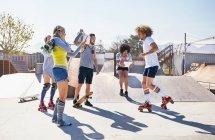 Друзья катаются на роликах и скейтборде в солнечном скейт-парке — стоковое фото