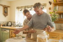 Playful mature couple baking, putting on apron in kitchen — Stock Photo