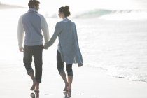 Young couple holding hands and walking on beach — Stock Photo