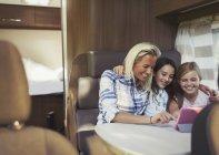 Sourire, mère et filles à l'aide d'une tablette numérique à l'intérieur du motor-home — Photo de stock