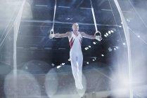 Gymnaste effectuant sur les anneaux de gymnastique en arène — Photo de stock